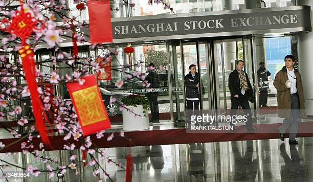 Chinese investors arrive at the Shanghai Stock Exchange as they pass near a blossom tree containing traditional red envelopes containing money for...
