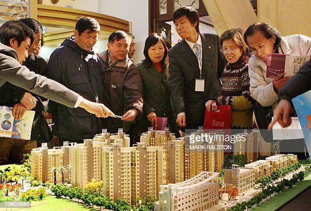Chinese investors talk with property salesmen for a new housing development at a real estate exhibition in Shanghai, 16 March 2007. China's...