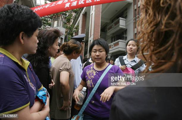 Chinese students are greeted by anxious parents outside the school gates after they finished their college entrance examinations at high school in...
