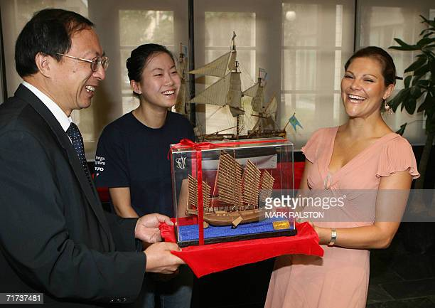 Crown Princess Victoria from Sweden, receives a gift of a traditional Chinese boat from Professor Xie Sengwu and a student at the opening of a...