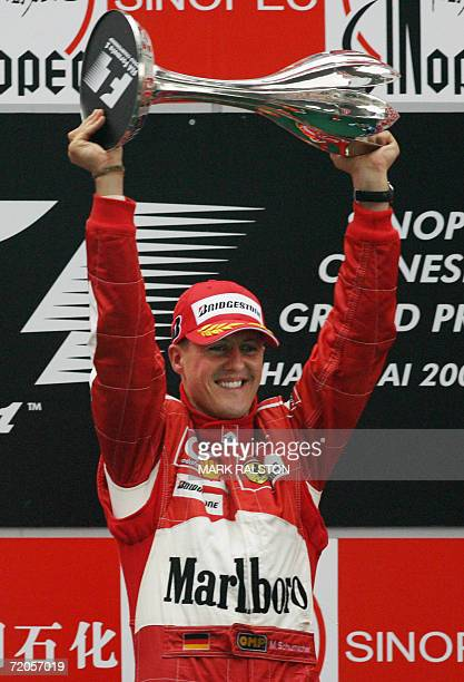 Ferrari driver Michael Schumacher of Germany celebrates with his trophy on the podium after winning the Chinese Grand Prix at the Shanghai...