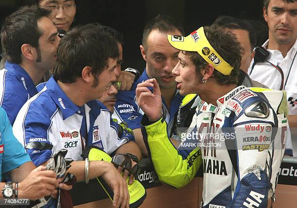 Italian MotoGP rider Valentino Rossi from the Yamaha team talks with his pit crew after finishing second in the MotoGP race at the Grand Prix of...