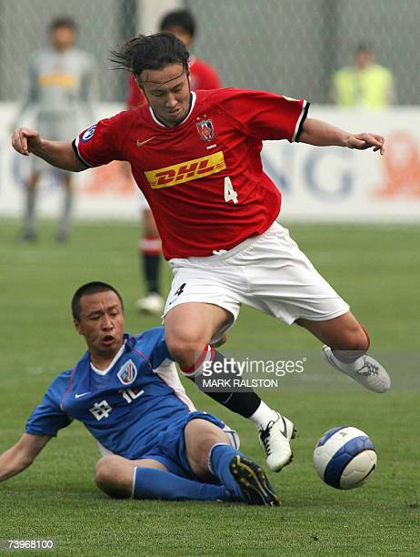 Marcus Tanaka from Japan's Urawa Reds, is tackled by Zheng Kewei from China's Shanghai Shenhua team during their Group E match of the AFC Champions...