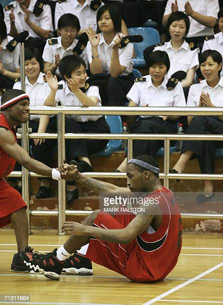 Member of the visiting USS Blue Ridge navy ship basketball team are watched by female navy officers during their game against the Chinese PLA navy...