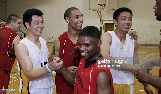Members of the visiting USS Blue Ridge navy ship basketball team congratulate members of the Chinese PLA navy team after beating them 86-68 points...