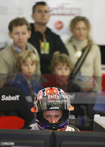 MotoGP rider Casey Stoner from Australia, is watched in the pits by family members before crashing his LCR Honda Team bike during the qualifying...