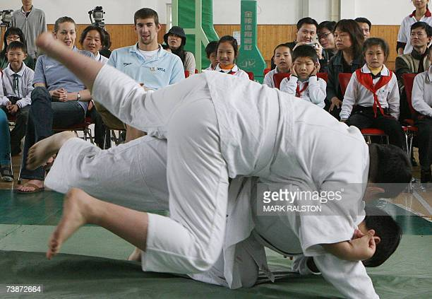 Olympic and World Swimming champions Katie Hoff and Michael Phelps watch as disabled students from the Pudong Special Needs School practice judo in...