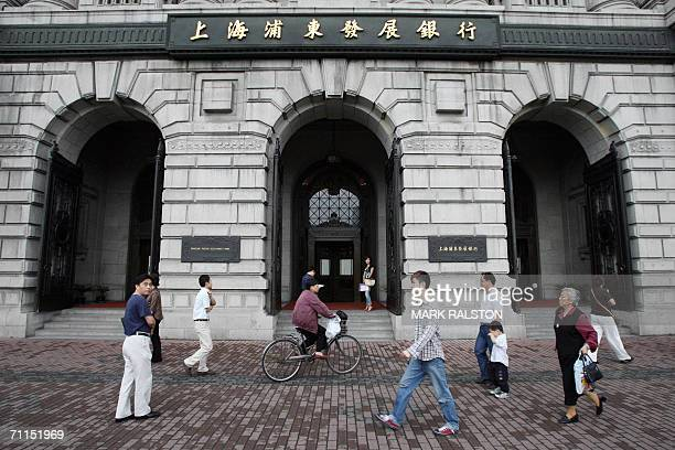 People walk past the headquarters of the Shanghai Pudong Development Bank which is housed in the old Hongkong and Shanghai Bank building in Shanghai...