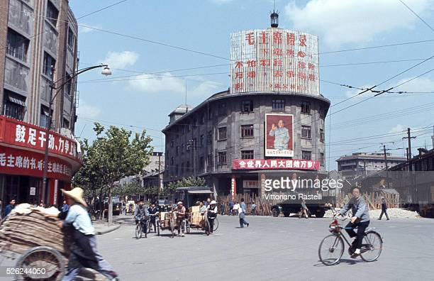 Shanghai China Street life in town with huge graffiti on the buildings hailing the Cultural Revolution and a huge portrait of President Mao Zedong in...