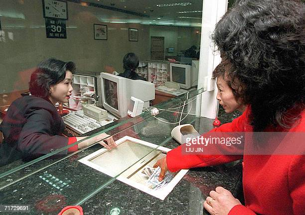This file photo dated 30 December 1999 shows bank customers making withdrawals at a counter in the Bank of China's branch in Shanghai China's central...