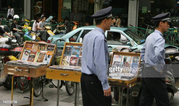 Two Chinese policemen walk past a street stall selling pirate movie dvd's and music cd's in Shanghai, 23 May 2007. The US told China that it was...