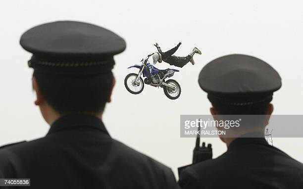 Two Chinese policemen watch as Australian rider Michael Norris does a stunt during a freestyle motocross demonstration at the Asian X Games event in...