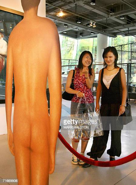 Two Shanghai girls share a laugh at the image titled 'Back of a Naked Man' painted onto a mirror by the Italian artist Michelangelo Pistoletto and on...