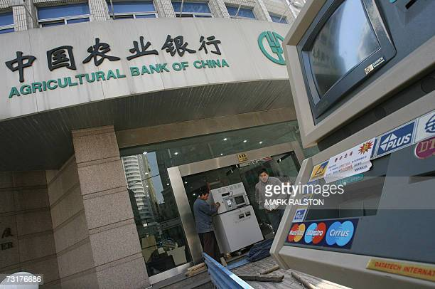 Workmen remove banking machines including ATM's from a branch of the Agricultural Bank of China in Shanghai 02 February 2007 A senior official from...