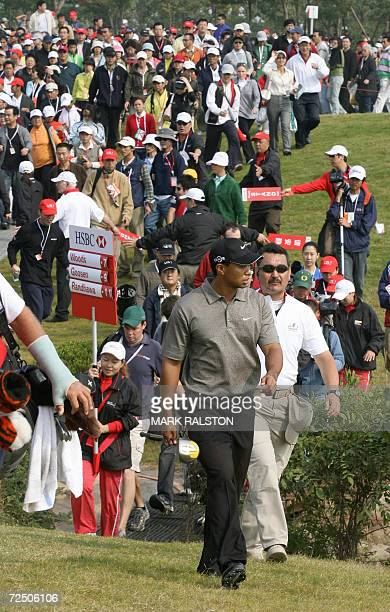 World number one Tiger Woods of the US, is followed by a large crowd during a wind swept third round of the HSBC Champions Golf tournament at the...