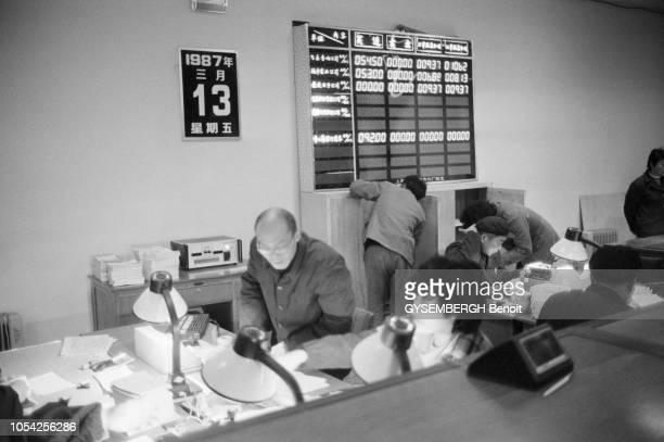 Shanghai Chine mars 1987 Les premiers courtiers de la bourse de Shanghai Ici clients et brokers Au mur le tableau des valeurs du stock exchange