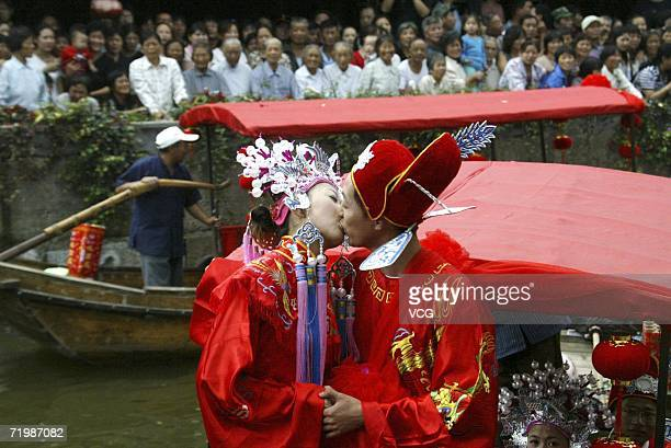 A Shanghai couple dressed for a traditional Chinese Wedding stand kiss on a boat at Water Village Wedding Ceremony on September 25 2006 at an ancient...