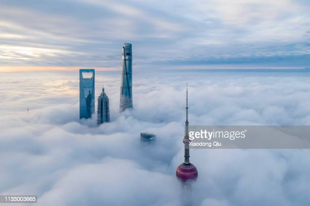 shanghai in clouds - skyscraper stock pictures, royalty-free photos & images