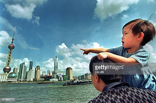 Shanghai kid carried by her father points at the skyscrapers of the Pudong district in Shanghai 10 September 2000 as they enjoy their time off during...