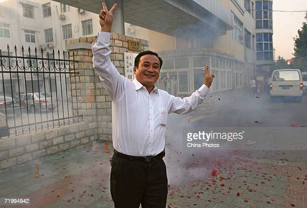 Shanghai resident Xu Ming who has been forced to relocate by the Shanghai government burns firecrackers to celebrate that Chen Liangyu secretary of...