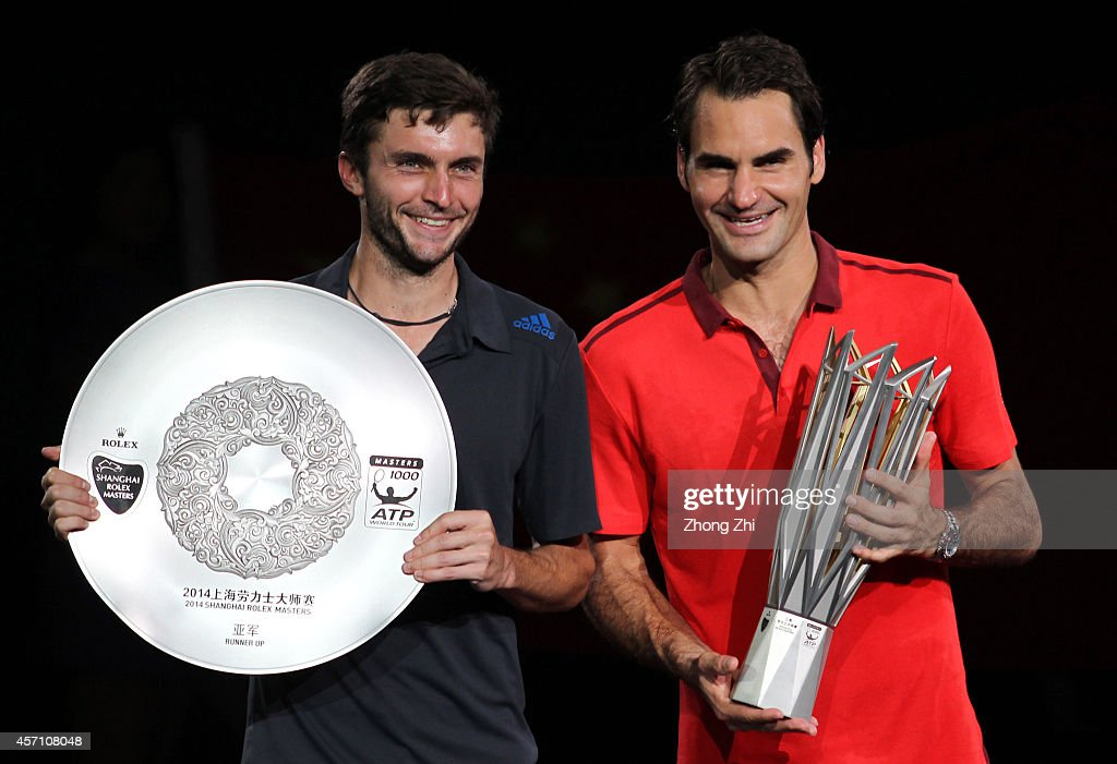 Shanghai Rolex Masters champion Roger Federer of Switzerland and runner-up Gilles Simon of France pose for photos with their trophies after the final during the day 8 of the Shanghai Rolex Masters at the Qi Zhong Tennis Center on October 12, 2014 in Shanghai, China.