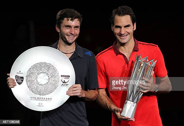 Shanghai Rolex Masters champion Roger Federer of Switzerland and runner-up Gilles Simon of France pose for photos with their trophies after the final...