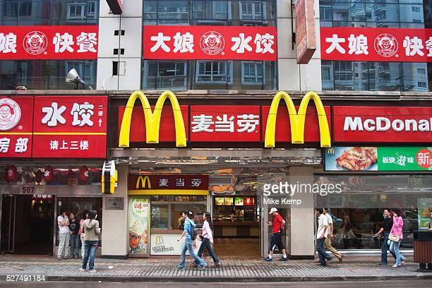 Shanghai scene, China. People walk past a MacDonalds Fast food restaurant on Fuzhou Lu. Convenience food is big business in China.