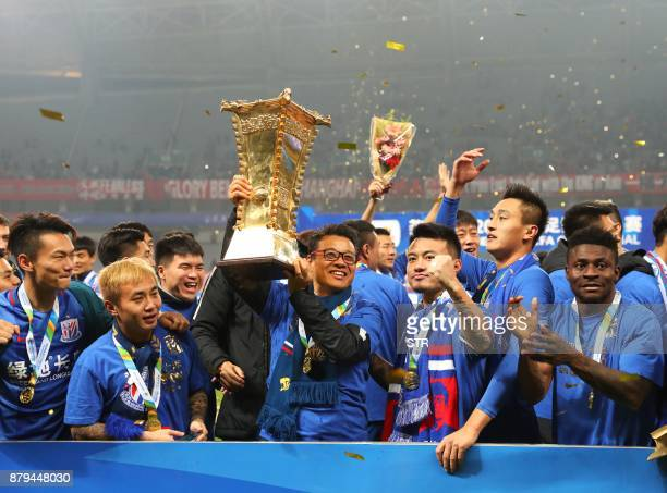 Shanghai Shenhua coach Wu Jingui holds the trophy after winning the Chinese FA Cup football match final in Shanghai on November 26 2017 Nigerian...
