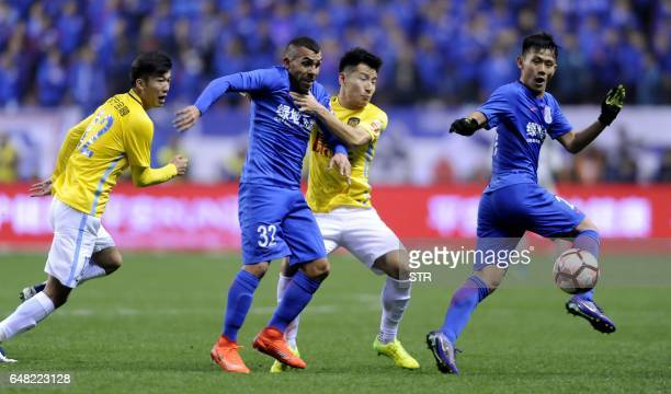 Shanghai Shenhua's Argentine striker Carlos Tevez fights for the ball with Yang Xiaotian of Jiangsu Suning during their Chinese Super League football...