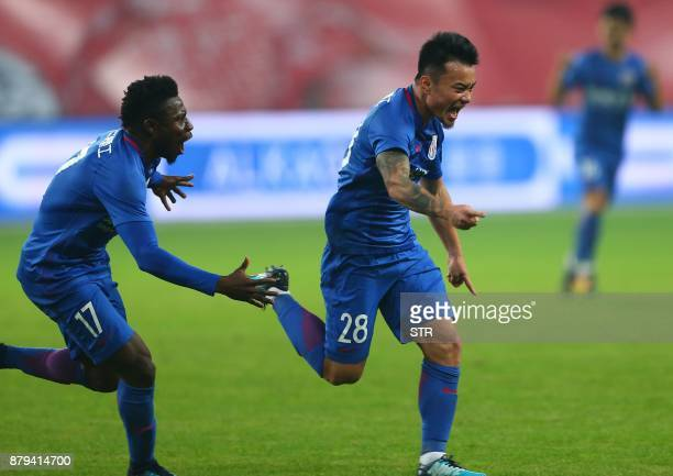 Shanghai Shenhua's Cao Yunding and Obafemi Martins celerate during their Chinese FA Cup football match against Shanghai SIPG in Shanghai on November...