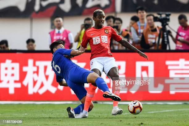 Shanghai Shenhua's Zhu Chenjie fights for the ball with Guangzhou Evergrande's Anderson Talisca during their Chinese Super League football match in...