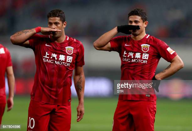 Shanghai SIPG's Brazilian forward Elkeson celebrates with his teammate Hulk after scoring a goal during the Chinese Super League match against...
