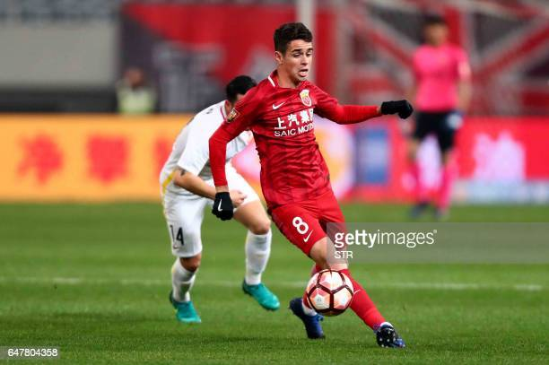 Shanghai SIPG's Brazilian midfielder Oscar controls the ball during the Chinese Super League match against Changchun Yatai in Shanghai on March 4...