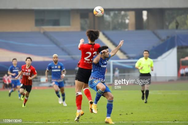 Shanghai SIPG's Fu Huan fights for the ball with Jiangsu Suning's Eder during their Chinese Super League football match in China's eastern Jiangsu...