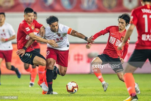 Shanghai SIPG's Hulk fights for the ball with Guangzhou Evergrande's Mei Fang during the Chinese Super League football match between Guangzhou...