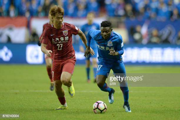 Shanghai SIPG's Shi Ke fights for the ball with Shanghai Shenhua's Obafemi Martins during their Chinese FA Cup football match in Shanghai on November...