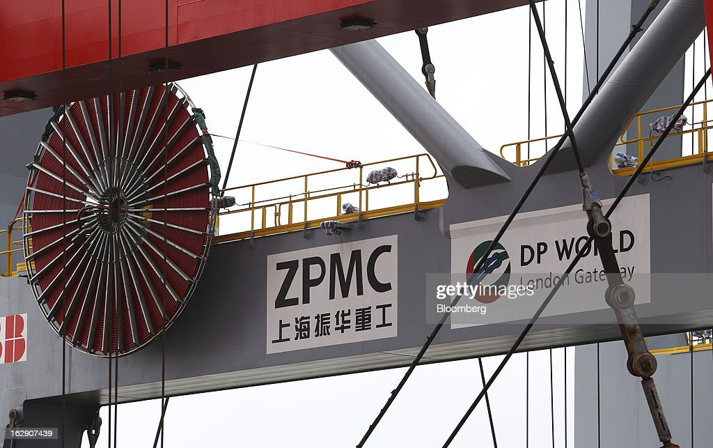 A Shanghai Zhenhua Heavy Industry Co. Ltd. (ZPMC) logo sits on display beside a DP World Ltd. logo on a ship-to-shore container crane aboard the Zhen Hua 26 heavy load carrier at the new DP World Ltd. London Gateway shipping terminal in Stanford-le-Hope, U.K., on Friday, March 1, 2013. DP World, which operates more than 60 terminals in six continents, said it is on track to open new capacity in Santos in Brazil, Jebel Ali in the United Arab Emirates and London Gateway in the U.K. this year. Photographer: Chris Ratcliffe/Bloomberg via Getty Images
