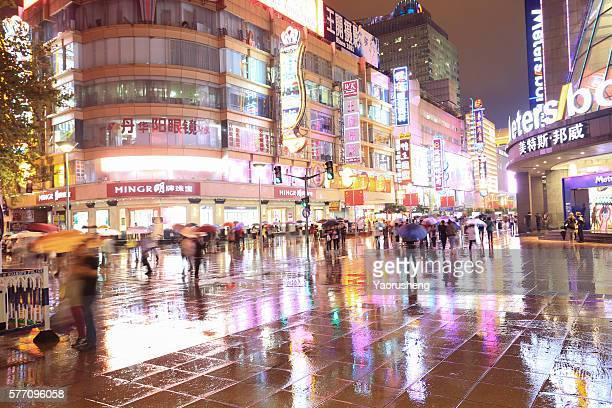 Shanghai,China-September 29,2015: tourist running rush on the Nanjing Road,Landmark of Shanghai City in rainny night