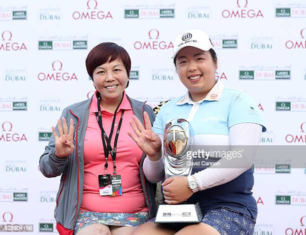 Shangshan Feng of China holds the trophy with her mother Yuyan Feng of China after her victory during the final round of the 2016 Omega Dubai Ladies...