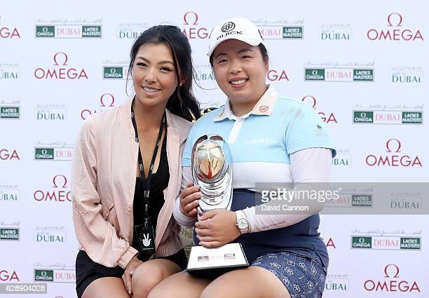 Shangshan Feng of China holds the trophy with Muni He of China after her victory during the final round of the 2016 Omega Dubai Ladies Masters on the...
