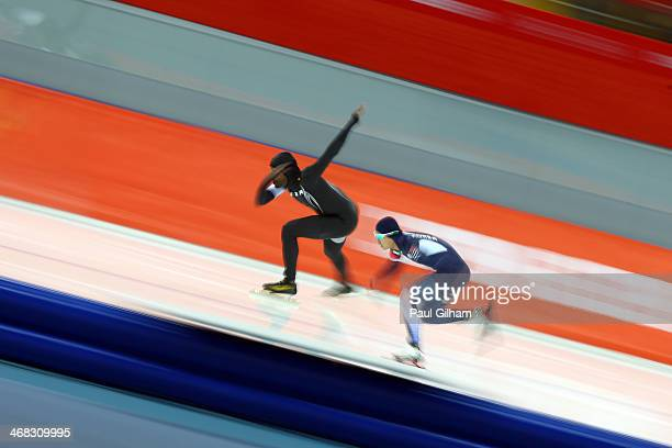 Shani Davis of the United States and Junho Kim of South Korea compete during the Men's 500 m Race 1 of 2 Speed Skating event during day 3 of the...