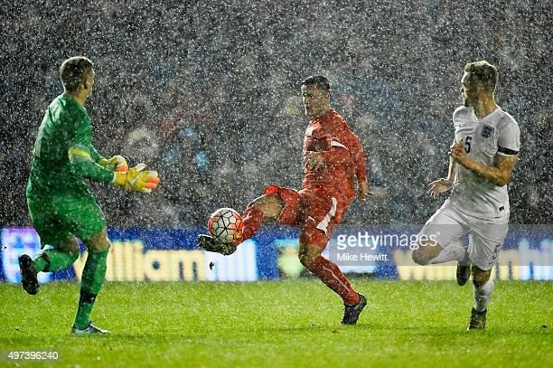 Shani Tarashaj of Switzerland chips the ball over goalkeeper Jordan Pickford of England to put his side ahead during a European Under 21 Qualifier...