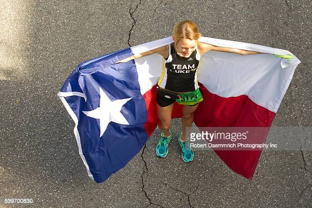 Shannon Bixler of Austin celebrates with a Texas flag after her first place women's finish in the Austin Marathon with a time of 3 hours two hours...