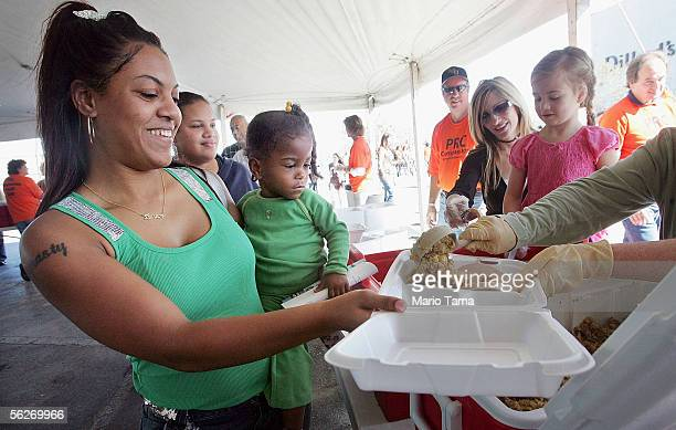 Shannon Blanchard and her daughter Aaliyah receive a free Thanksgiving meal of turkey and stuffing from Christian volunteers November 24 2005 in New...