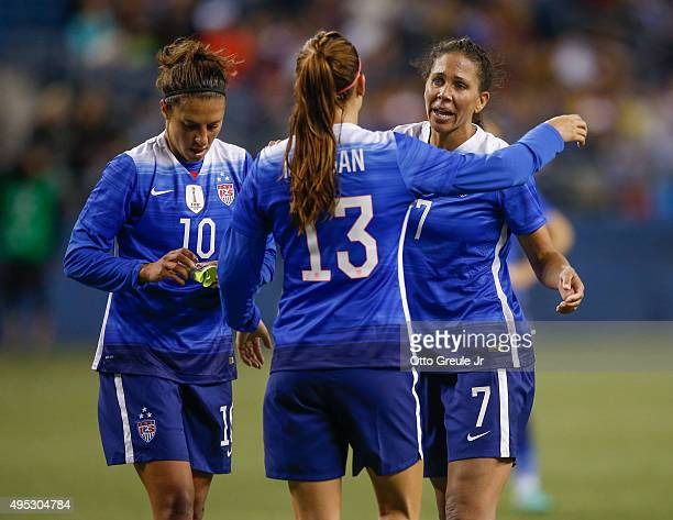 Shannon Boxx of the United States is congratulated by Alex Morgan and Carli Lloyd as she is removed from the match in the first half against Brazil...