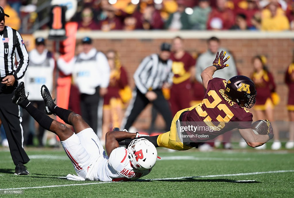 Shannon Brooks #23 of the Minnesota Golden Gophers is tackled by Saquan Hampton #9 of the Rutgers Scarlet Knights during the first quarter of the game on October 22, 2016 at TCF Bank Stadium in Minneapolis, Minnesota.