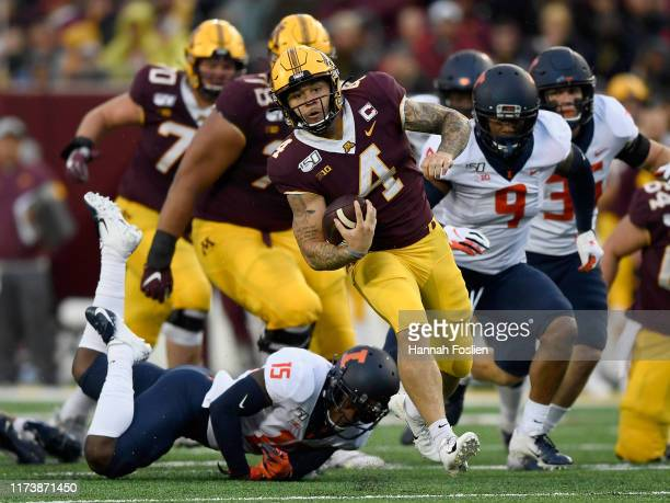 Shannon Brooks of the Minnesota Gophers avoids a tackle by Delano Ware of the Illinois Fighting Illini during the third quarter of the game at TCF...