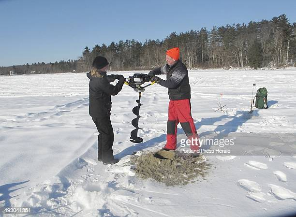 Shannon Bryan and John Peterson of the Kittery Trading post use a powered auger to drill a hole into the ice staff photo