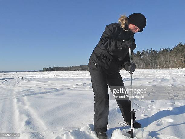 Shannon Bryan uses a hand auger to drill a hole into the ice staff photo