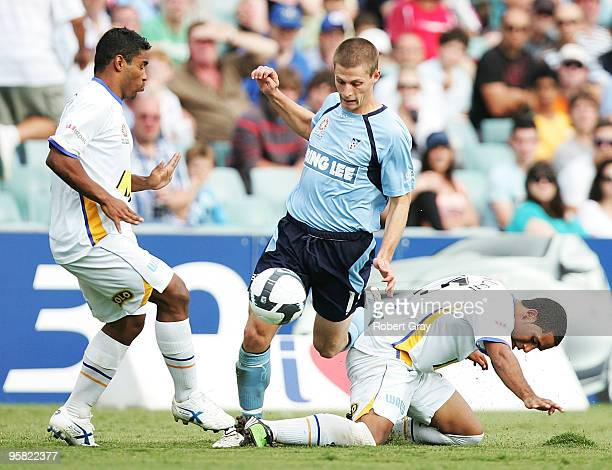 Shannon Cole of Sydney FC squeezes through a gap between defenders Anderson Alves da Silva and Tahj Minniecon of the Gold Coast during the round 23...